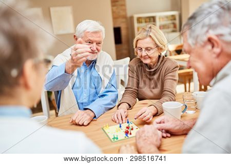 Seniors as retired couple plays with friends a board game in retirement home or at home