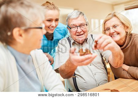 Group of seniors with dementia playing with a wooden puzzle in nursing home or at home