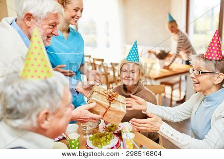 Senior woman as a birthday girl gets a present at her birthday party