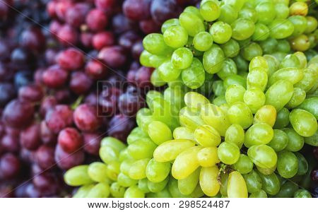 Bunch Of Fresh Green Grapes And Red-black Grapes In A Local Market. Healthy Fruits
