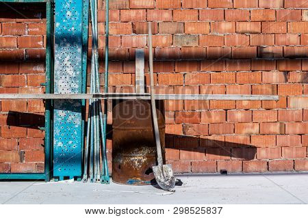 Rusty Metal Drum, Scaffold Materials And Shovel In Front Of A Brick Wall.