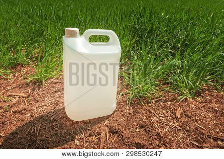 Blank Pesticide Jug Container Mock Up In Wheatgrass Field. Using Chemical In Crop Protection Agricul