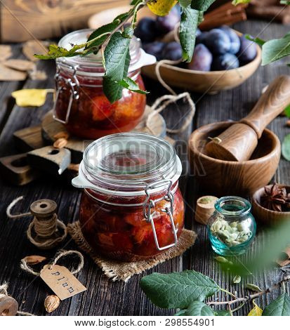Two Glass Jars With Homemade Canned Plums Jam, Marmalade, Jelly On Rustic Wooden Table With Cardamon