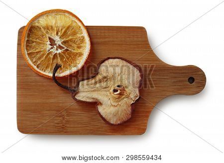 Still Life With Dried Slices Of Orange And Sweet Pear On The Wooden Cutting Board Against White Back