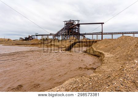 Rusty Pipe On The River Bank, From Which Sewage Flows, Dirty Sand Slurry, And Stationary Rusty Gravi