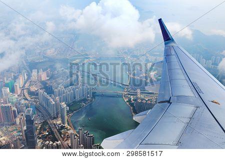 Airplane Flies Over Hong Kong. Passenger Jet Plane Flying Above Urban Scene. Hongkong Flight. Asian