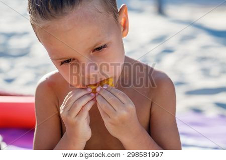 Child Boy Is Eating Fruits On The Beach