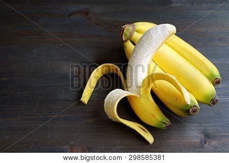 One peeled banana on a bunch of bananas isolated on dark brown wooden table with copy space poster