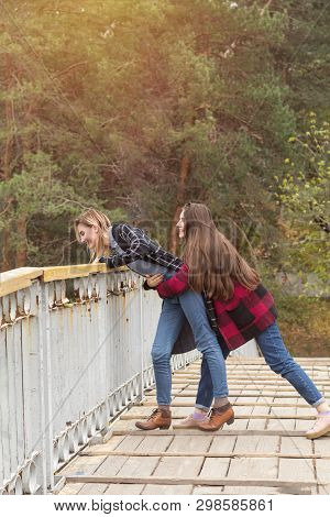 Two Cute Beautiful Young Women On The Wooden Bridge In The Autumn City Park. Emotion And Activity.