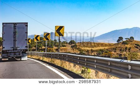 Truck Driving On A Road With Dangerous Curve Signage, Wonderful Sunny Day To Enjoy The Scenery In Th