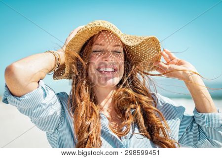 Closeup face of mature woman wearing straw hat enjoying the sun at beach. Happy woman smiling during summer vacation at sea.Beautiful lady relaxing at beach while holding large brim for the wind.