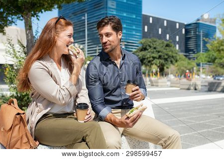 Smiling man with his girlfriend having lunch outdoor sitting in a square. Happy couple enjoying sandwich and disposable cup coffee during lunch break. Man in conversation with woman outside office.