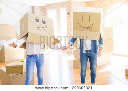 Couple having fun at new apartment wearing boxes with funny faces over head