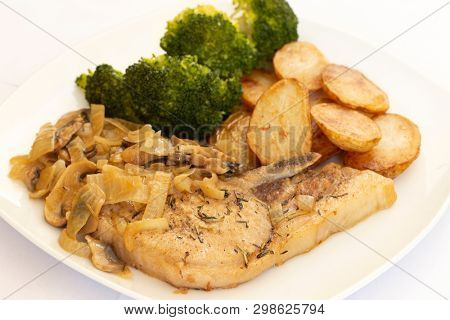 Loin pork chop with mushroom, cream, onion and cider sauce, served with broccoli and fried baby potatoes