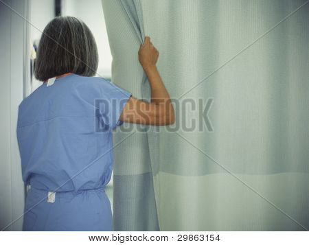 Female doctor opening hospital room curtains