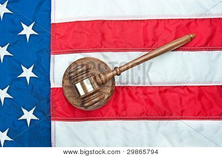 A gavel and sound block on an American flag representing the legal system and any law inference in the USA
