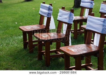 Decorated Chairs With Black Fabric And Big Pink Satin Bows. Silk Bow Tied On Back Of Chair In Party