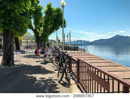 Luino, Lombardy, Italy - April 30, 2019: People Resting At The Outdoor Bar On The Lakefront Of Luino