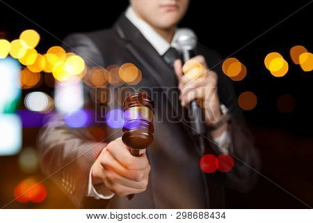 Presenter With A Microphone In His Hand Holds An Auction On Blurred Background.