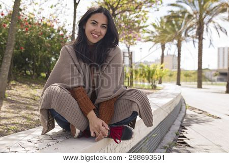 Happy Pretty Woman Posing At Camera And Sitting On Parapet. Young Lady Looking At Camera And Sitting