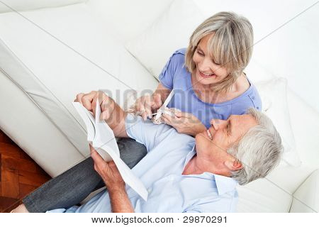 Man showing senior woman knitting patterns at home in a book