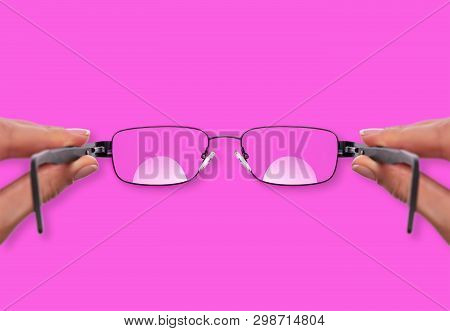 Glasses In A Female Hand On A Pink Background.