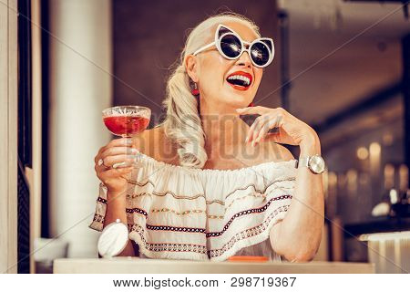 Laughing Long-haired Senior Woman Wearing Weird Glasses