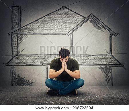 Stressed Man Sitting On The Street With Hands Folded Together Praying For A Home. Poverty And Homele