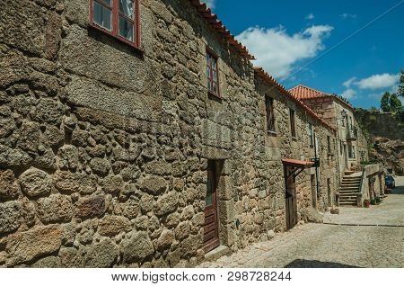 Gothic House Made Of Stone With Wooden Door And Deserted Alley On Slope, In A Sunny Day At Sortelha.