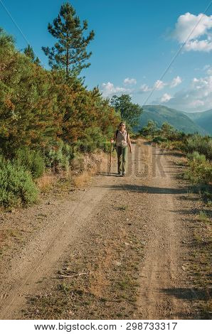 Serra Da Estrela, Portugal - July 14, 2018. Woman Hiking On Dirt Road Over Hilly Terrain Covered By