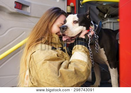 Image of firewoman with dog standing near fire truck at station