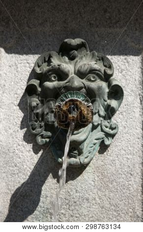 Public Water Fountain Outside The Basilica Of San Giacomo Framed By A Side Street In Bellagio, Lake