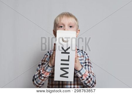 Little Blond Boy Is Holding A Big White Carton Milk Package. Light Background