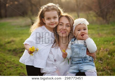 Happy Family Walks In The Spring Meadow