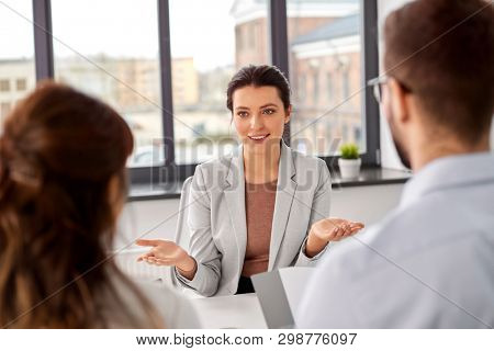 new job, hiring and employment concept - team of recruiters having interview with female employee at office