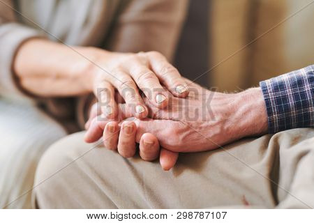 Senior male han between those of his mature wife or caregiver as symbol of support, care and love