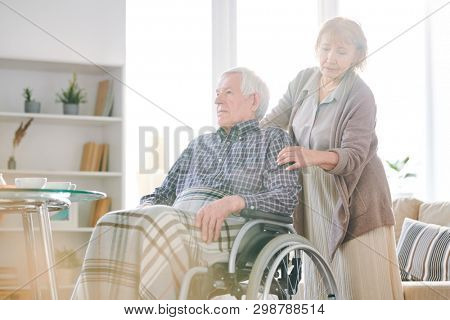 Mature female caregiver in casualwear taking care of aged disable man with grey hair in wheelchair