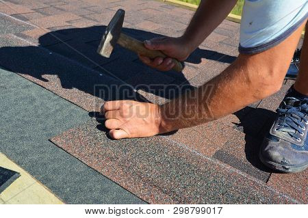 Roofing Contractor Installing Roof Tiles, Asphalt Shingles With Hammer And Nails. Roofing Constructi