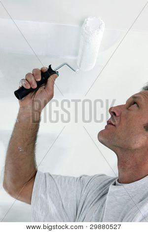 Decorator repainting ceiling