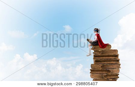 Little Child In Mask And Cape Sittting On Pile Of Old Books In Sky And Reading