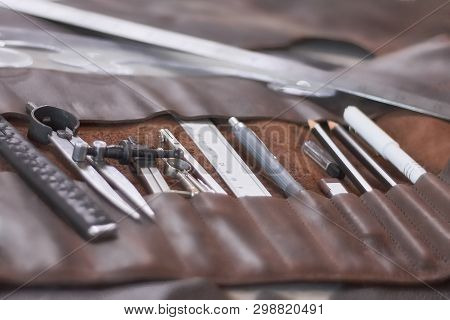 Leather crafting DIY tools and templates on workbench. Instruments in brown leather case. poster