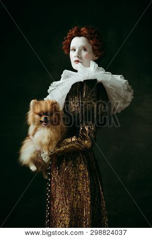 Brilliance view. Medieval redhead young woman in golden vintage clothing as a duchess holding puppy and standing on dark green background. Concept of comparison of eras, modernity and renaissance. poster