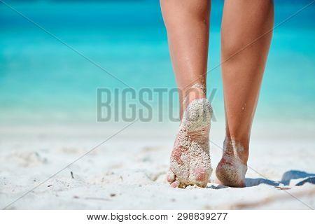 Woman walking on tropical white sand beach. Summer vacation at Maldives.