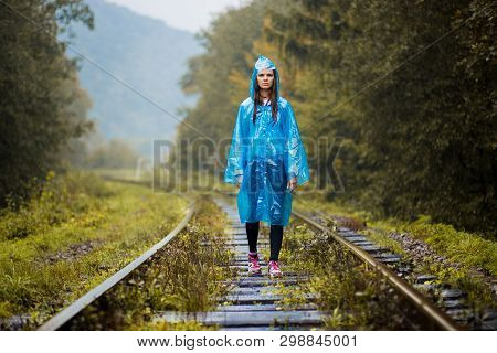 Girl Traveller Wearing Blue Jacket And Go By Forest Railway. Autumn And Raining Season With Dark Gre