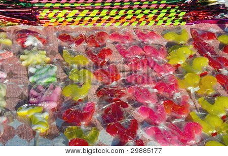 Colorful candy packed in polyethylene sell outdoor street fair in market. poster