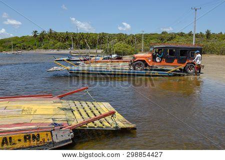 Man Trasporting A Car On A Raft In The River Near Pipa On Brazil