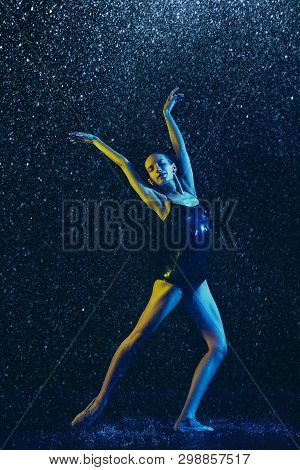 Young Female Ballet Dancer Performing Under Water Drops And Spray. Caucasian Model Dancing In Neon L