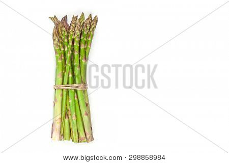 Bunch of fresh raw garden asparagus isolated on white background. Green spring vegetables. Edible sprouts of asparagus. Top view with copy space.