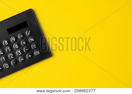 Black Minimal Calculator On Solid Yellow Background With Copy Space Using For Financial Activity, Ac