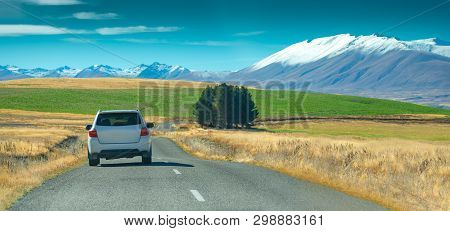 A Silver Crossover Car Driving Fast On The Countryside Asphalt Road Against Blue Sky With White Clou